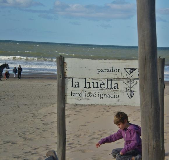 Menino brincando na praia embaixo da placa do Parador La Huella no Uruguai Blog Vem Por Aqui