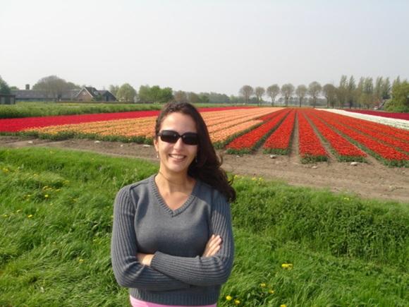 Érika Schunk diante de um campo de tulipas na Holanda Blog Vem Por Aqui