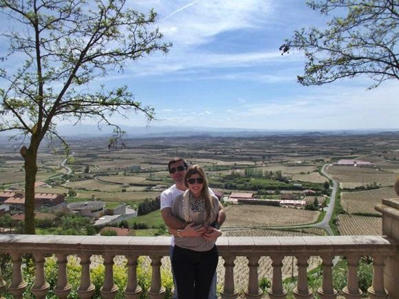 Igor Gimenes e Luciana Viana diante da vista dos vinhedos Blog Vem Por Aqui