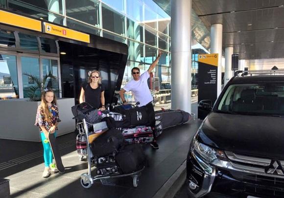 Bella, a mãe e o pai, mais os carrinhos com bagagem, na saída do aeroporto Blog Vem Por Aqui