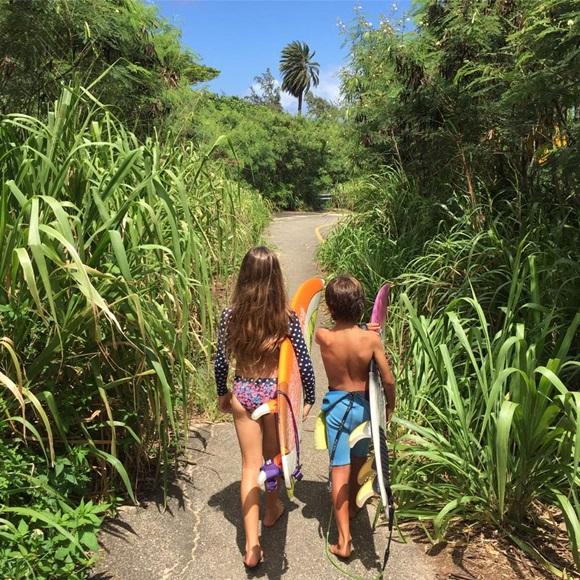 Bella e um amiguinho andando, de costas pra câmera, numa trilha do Havaí Blog Vem Por Aqui