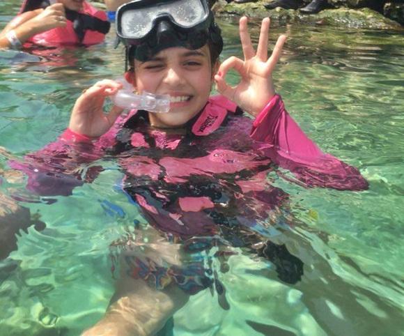 Laura na água, de máscara e snorkel, fazendo sinal de OK Blog Vem Por Aqui