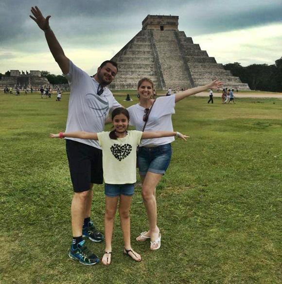 Laura e os pais, de braços abertos, em frente a uma pirâmide em Cancún Blog Vem Por Aqui
