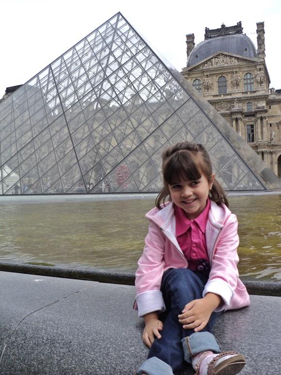 Laura posando sentada, em frente à pirâmide do Louvre Blog Vem Por Aqui