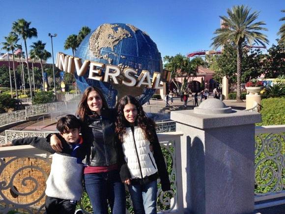 Arthur, a mãe e a irmã em frente ao símbolo da Universal Blog Vem Por Aqui