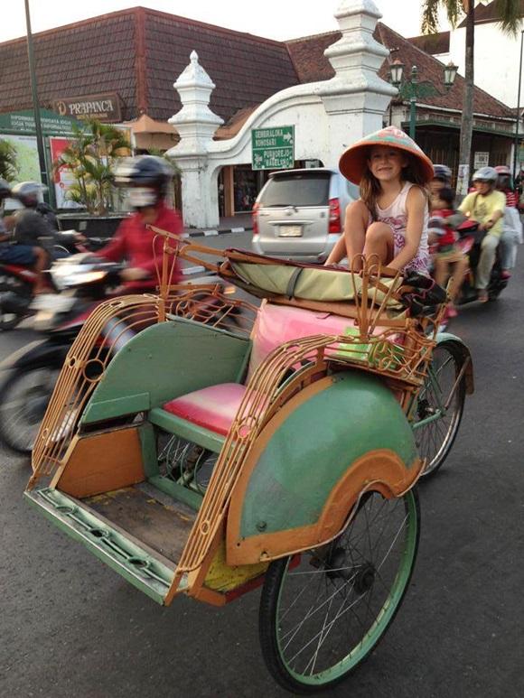 Izabelle num tuk tuk na Indonésia com um chapéu típico Blog Vem Por Aqui