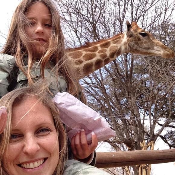 Izabelle sentada nos ombros da mãe com uma girafa ao fundo Blog Vem Por Aqui