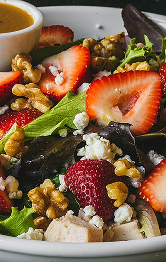 Salada com vegetais, nozes e morangos e potinho de molho no fundo do prato Blog Vem Por Aqui