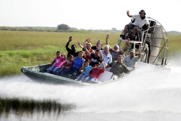 Grupo dentro de um airboat e o veículo levantando água no rio Blog Vem Por Aqui