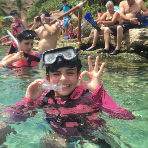 Laura Tavares com máscara e snorkel, dentro da água, piscando um olho e fazendo sinal de ok com a mão Blog Vem Por Aqui