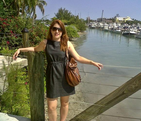 Érika de vestido preto, bolsa caramelo e óculos escuros, encostada numa cerca com fios de metal com o mar e os barcos ao fundo Blog Vem Por AquiFot
