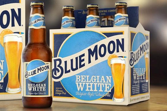 Propaganda da cerveja Blue Moon com caixa de seis ao fundo e uma garrafa um pouco a frente na lateral Blog Vem Por Aqui