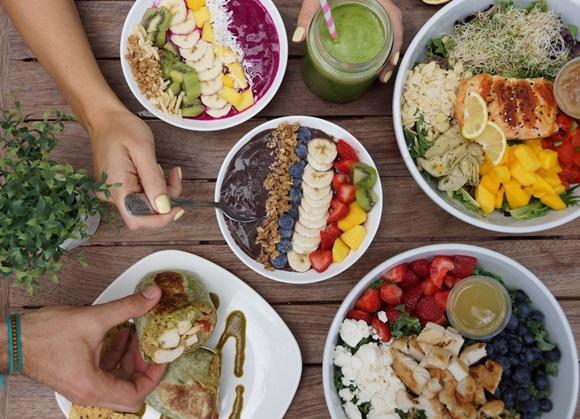 Mesa cheia de pratos com muitas frutas e verduras. Dois de açaí com frutas, copo de suco verde, dois bowls maiores com salada com um pedaço de salmão e prato com sanduíche Blog Vem Por Aqui