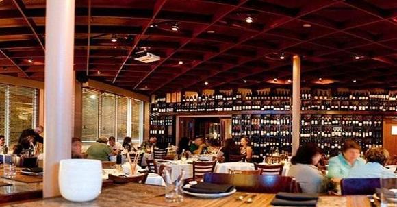 Foto interna do Graziano´s com mesas e parede de vinhos ao fundo Blog Vem Por Aqui