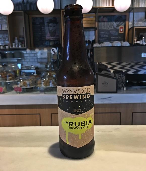 Garrafa de cerveja La Rubia com balcão do café ao fundo Blog Vem Por Aqui