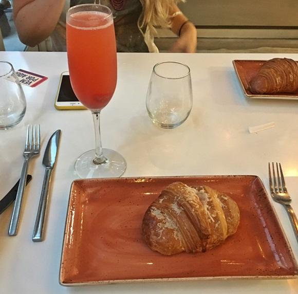Mesa com talhares, prato com croissant de presunto e queijo e, ao fundo, uma taça com Bellini de morango Blog Vem Por Aqui