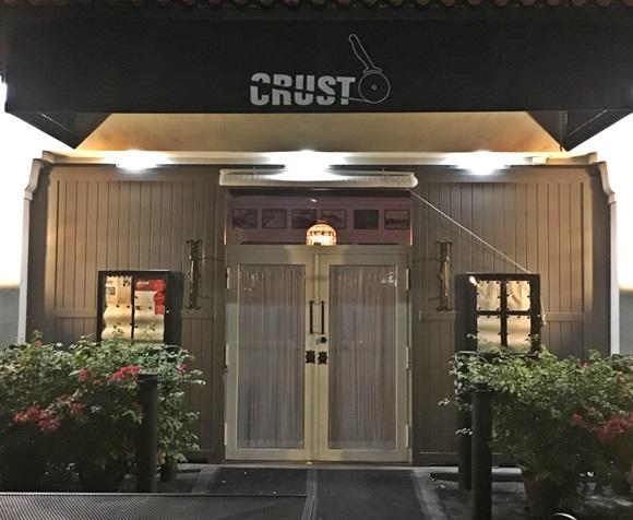 Fachada do Crust com parede de madeira pinta de branco na lateral e porta dupla de vidro no meio. Em cima a placa com nome do restaurante e a logo de um cortador de pizza em preto. Blog Vem Por Aqui