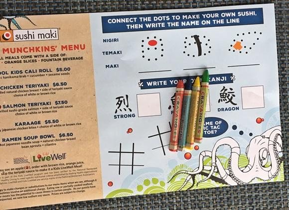 Jogo americano de papel com cardápio para crianças e, ao lado, desenhos para colori com os gizes de cera que estão sobre ele Blog Vem Por Aqui