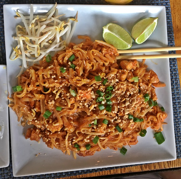 Prato com pad thai (macarrão oriental), brotos de feijão e limões na parte superior Blog Vem Por Aqui