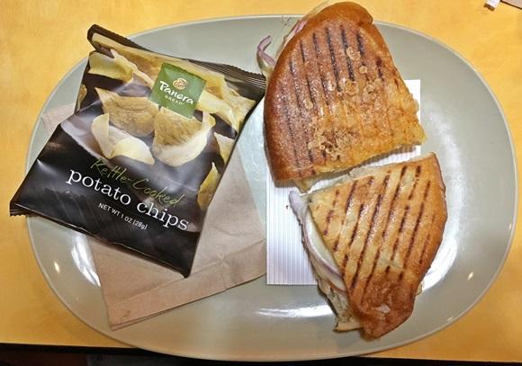 Prato com pacote de batatas fritas e sanduíche partido em duas metades de pão tostado Blog Vem Por Aqui
