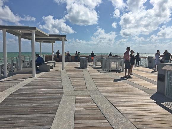 Pier do South Pointe Park com pessoas nas laterais e céu azul acima Blog Vem Por Aqui