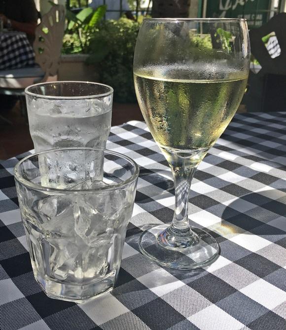 Taça de vinho quase cheia, em cima da mesa com toalha xadrez, com copo de água ao fundo e de gelo do lado esquerdo Blog Vem Por Aqui
