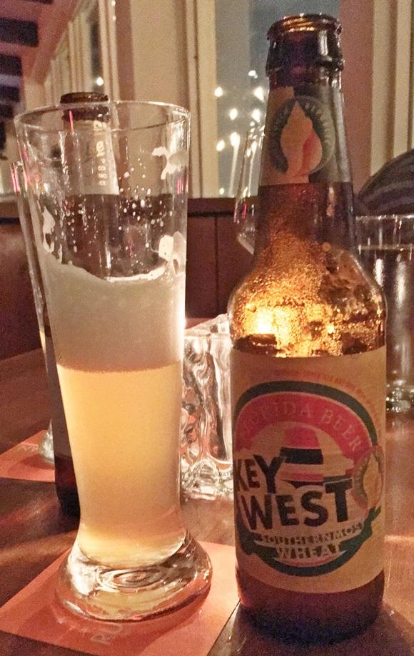 Taça com cerveja e garrafa de cerveja Key West ao lado Blog Vem Por Aqui