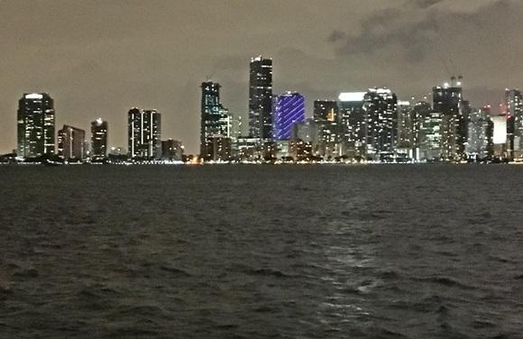 Mar com prédios iluminados ao fundo, vistos do Rusty Pelican Blog Vem Por Aqui