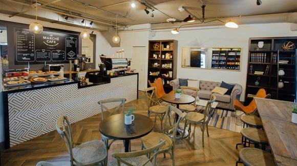 Área interna do Le Marché Café com balcão, mesas e sofá ao fundo Blog Vem Por Aqui