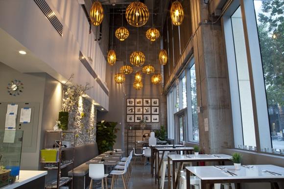 Área interna do Bachour Bakery + Bistrô com lustres grades e em tamanhos diferentes pendendo do teto, mais mesas e cadeiras Blog Vem Por Aqui