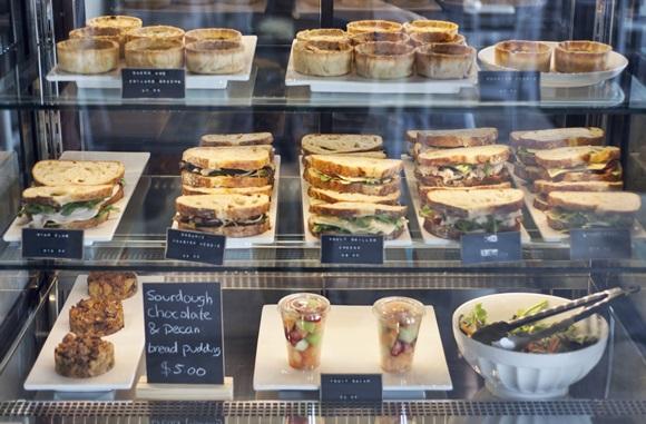 Balcão com produtos do Le Marché Café, sanduíches no meio, tortinhas em cima, salada de fruta e salada salgada embaixo Blog Vem Por Aqui