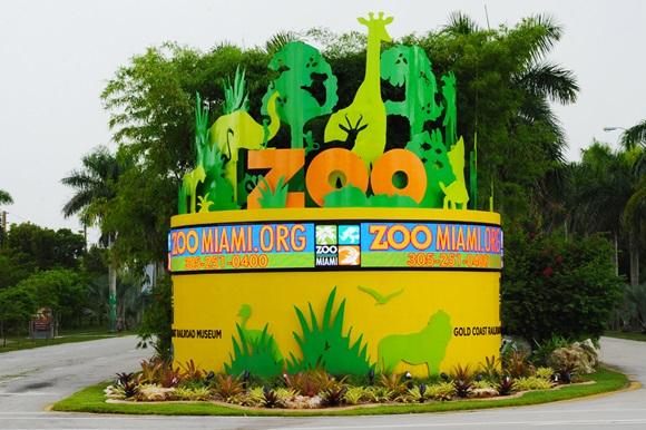 Entrada no Zoo Miami com monumento em amarelo cheio de bichos estilizados e o nome do lugar Blog Vem Por Aqui