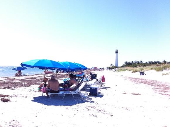 Areia com reflexo solar, barracas azuis e pessoas sentadas nas espriguiçadeiras com farol ao fundo no Bill Bags Cape State Park Blog Vem Por Aqui