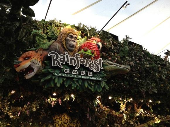 Fachada do Rainforest Café com a logo do restaurante que tem tigre, macaco e sapo associados ao nome do lugar Blog Vem Por Aqui