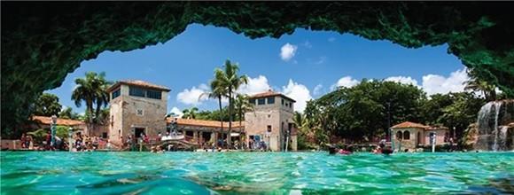 Imagem de dentro de uma caverna da Venetian Pool com prédios ao fundo e água na frente Blog Vem Por Aqui