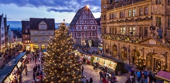 Vista aérea da praça da cidade com barraquinhas do mercado de Natal, árvore natalina e pessoas circulando Blog Vem Por Aqui