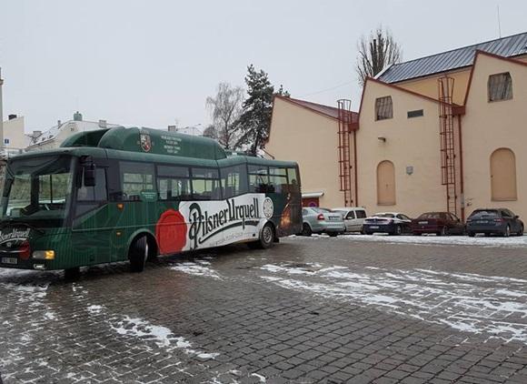 Fábrica da cerveja Pilsner Urquell com ônibus plotado de verde com a marca da cerveja na frente Blog Vem Por Aqui
