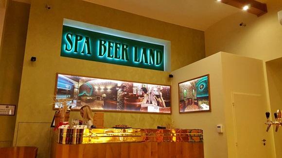 Recepção do Spa Beer Land com placa com nome do lugar acima e recepcionista atrás do balcão Blog Vem Por Aqui