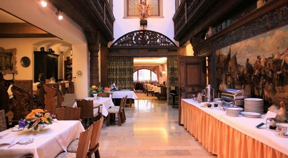 Restaurante do hotel vazio, com mesas com toalhas brancas e arranjos de flores e mesa maior de buffet do lado direito, com um mural pintado atrás e pratos e bandejas em cima Blog Vem Por Aqui