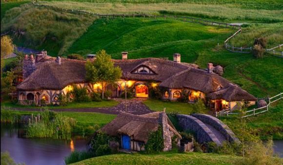 Casas de estilo medieval iluminadas em frente a um rio e no meio de uma grande pastagem verde Blog Vem Por Aqui