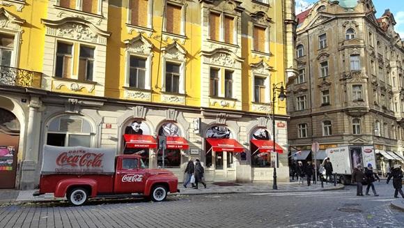 Prédio amarelo com janelas brancas no bairro judeu, com bar de toldos vermelhos na calçada e caminhão antigo da Coca-Cola estacionado na frente Blog Vem Por Aqui