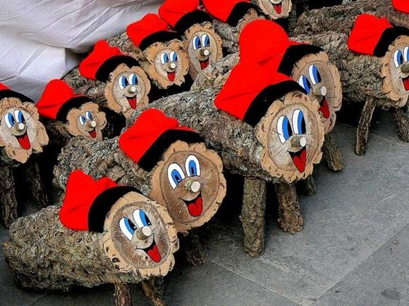 Duas fileiras de caga tiós, troncos de árvore decorados com olhos, boca, nariz e gorro vermelho Blog Vem Por Aqui