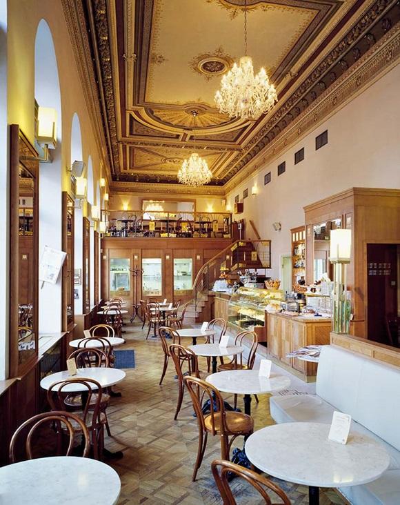 Salão interno do Café Savoy com teto alto e lustres de cristal e mesas com cadeiras ao longo do salão, em frente ao balcão de madeira Blog Vem Por Aqui