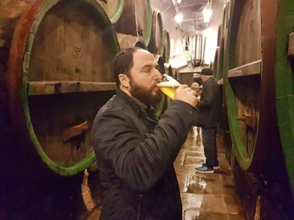 Paulo tomando cerveja em frente aos barris de madeira da fábrica Blog Vem Por Aqui
