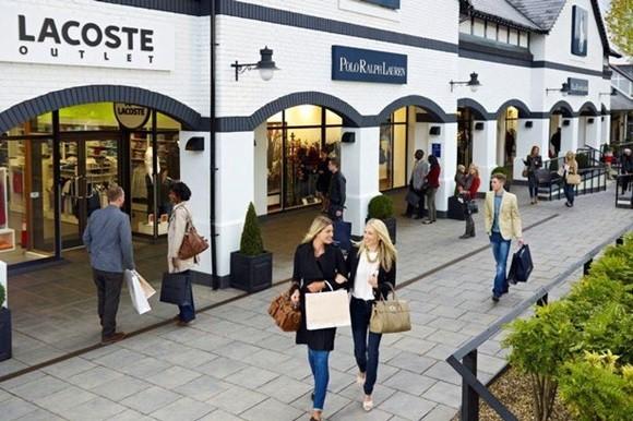 Pessoas passeando em frente à loja da Lacoste no Cheshire Oaks com outras lojas ao fundo Blog Vem Por Aqui