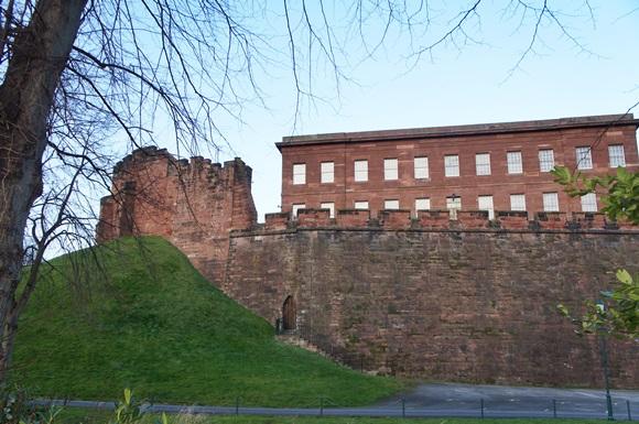 Parte da muralha de Chester com um prédio de janelas brancas ao fundo e um barranco com grama verde à frente Blog Vem Por Aqui