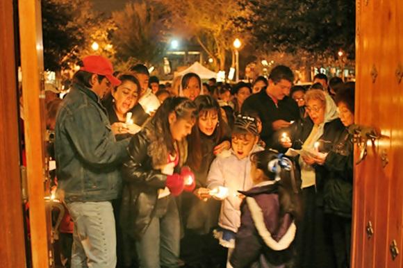 Pessoas com velas na porta de uma casa Blog Vem Por Aqui