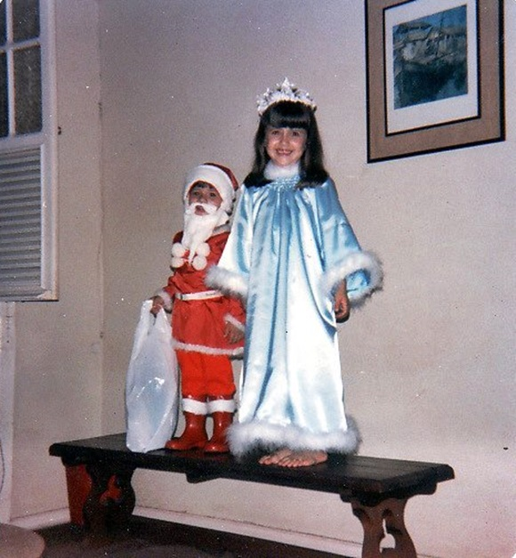 Eu, vestida de anjo, e meu irmão mais novo, vestido de Papai Noel, em cima de um banco, fazendo um teatrinho no Natal Blog Vem Por Aqui