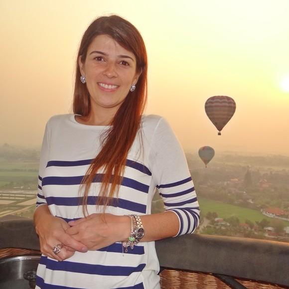 Carolina numa sacada com balões ao fundo Blog Vem Por Aqui