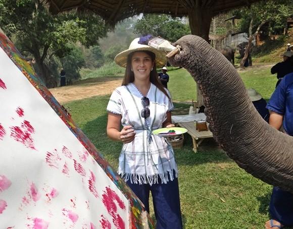 Carolina Silva com um prato cheio de tinta e a tromba de um elefante segurando um pincel e dando pinceladas numa grande folha branca Blog Vem Por Aqui